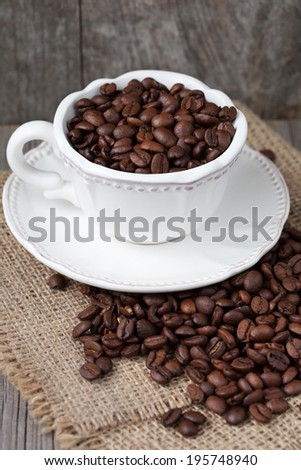 Cup full of coffee beans on old wooden background, selective focus