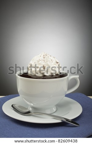 cup full of hot liquid with cream on it