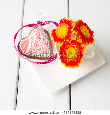 Cup full of pink gerbera  flowers and  heart shape cookie on white wooden table. - stock photo