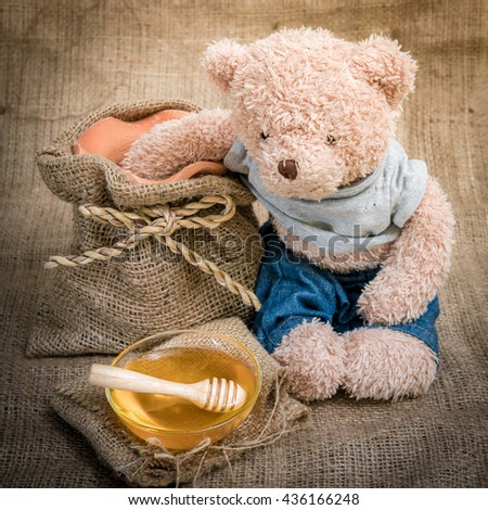 cup honey on sackcloth with Teddy Bear  Vintage Style and selective focus - stock photo