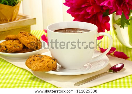 cup hot chocolate, cookies  and flowers on table in cafe - stock photo