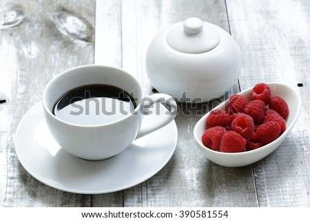 cup if coffee and plate with berries for breakfast   - stock photo