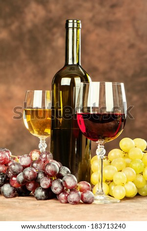 cup of a red wine in front of grape, bottle and glass of white wine - stock photo