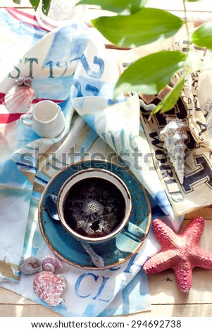 Cup of americano coffee set with seashells, milk and sugar on marine themed napkin. Holiday by tropical sea relaxation concept. Brightly sunlit setting, natural light. - stock photo