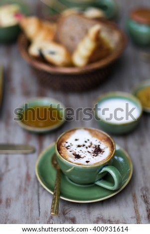 Cup of aroma cappuccino at breakfast with croissants - stock photo