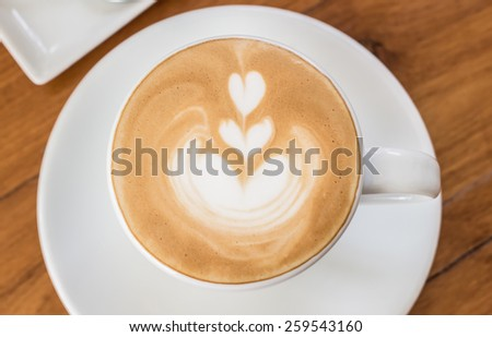 Cup of Art Latte coffee on the wooden desk  - stock photo