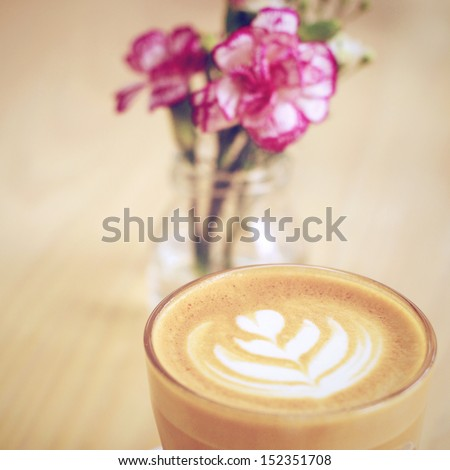 Cup of art latte or cappuccino coffee with flower, retro filter effect - stock photo