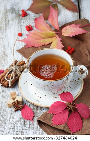 Cup of autumn tea on light  wooden background. Selective focus