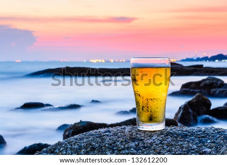 Cup of beer standing on the rock at sea, Thailand - stock photo