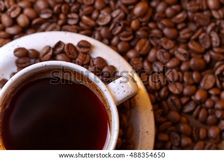 Cup of black coffee and roasted beans