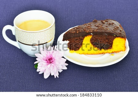 Cup of black coffee, chocolate orange cake and chrysanthemum flower on a blue tablecloth - stock photo