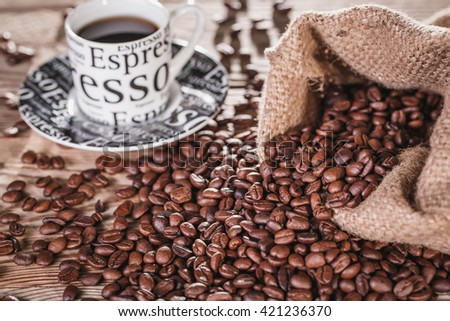 Cup of black coffee in cup on wooden table next to sack of coffee beans.