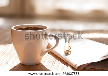 Cup of black coffee, newspaper and a pen against the window in the morning - stock photo