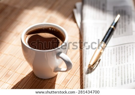 Cup of black coffee, newspaper and a pen the morning - stock photo