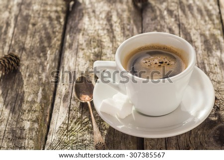Cup of black coffee on wooden board and pines
