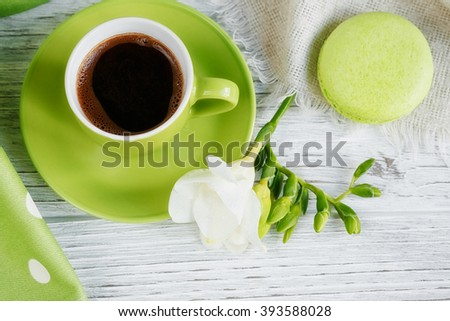 Cup of black coffee, white freesia flowers and sweet pastel french macaroons on white wooden table - stock photo