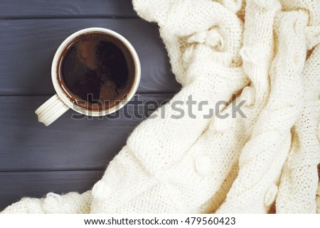 Cup of black coffee, white knitted plaid, on white wooden background