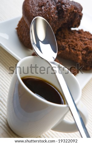Cup of black coffee with a fresh chocolate muffin