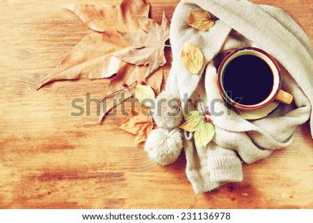 Cup of black coffee with autumn leaves, a warm scarf and old book on wooden background.  - stock photo