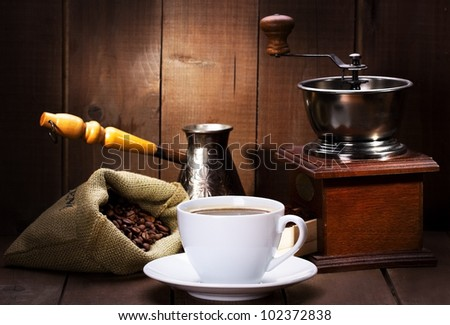 cup of black coffee with beans and old grinder
