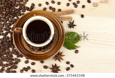 Cup of black coffee with cinnamon, green leaves, stars of anise and coffee beans on a wooden background - stock photo