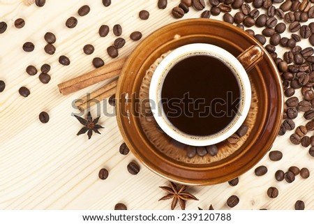 Cup of black coffee with cinnamon, stars of anise and coffee beans on a wooden background  - stock photo