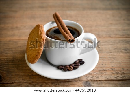 Cup of black coffee with cookie, cinnamon stick and coffee beans on old vintage wooden table - stock photo