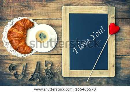 Cup of black coffee with croissant, blackboard and heart decoration on rustic wooden background. romantic french breakfast. Valentines Day card concept with sample text I love You! - stock photo
