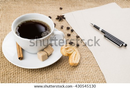 Cup of black coffee with foam, cookie, brown sugar, craft paper, pen, beans, anise star and cinnamon stick on sackcloth background - stock photo