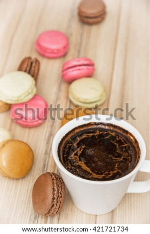 Cup of black coffee with french colorful macarons. Sweet delight. Vertical composition. Food and drink. Tasty macarons. Sweet food. - stock photo