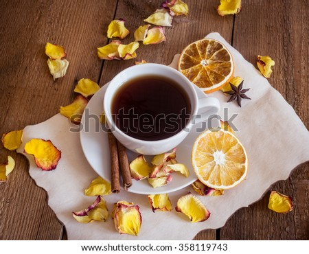 Cup of black tea, dried oranges, dry rose petals and homemade cookies on wooden background