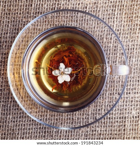 cup of black tea with apricot flower on canvas , top view