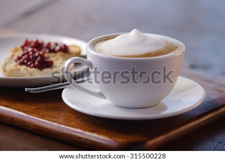 cup of cappuccino and a glass of orange juice in the background - stock photo