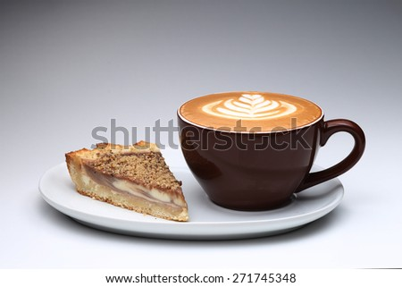 Cup of cappuccino and a piece of cake. Latte art. Gray background - stock photo