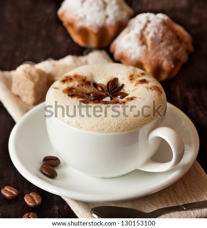 Cup of cappuccino and cake on a dark background close up.