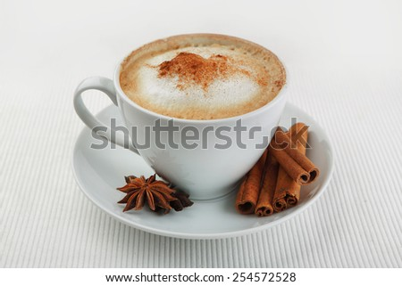 Cup of cappuccino and saucer on the table on a velvet drape, cinnamon and star anise - stock photo