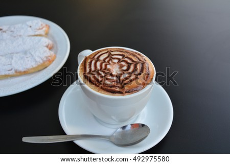 Cup of cappuccino and sweet cake on a black background