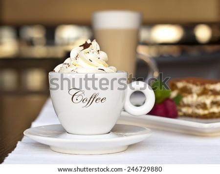 Cup of cappuccino and tiramisu cake in cafe - stock photo