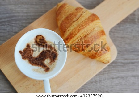 Cup of cappuccino and yummy croissant on wooden table