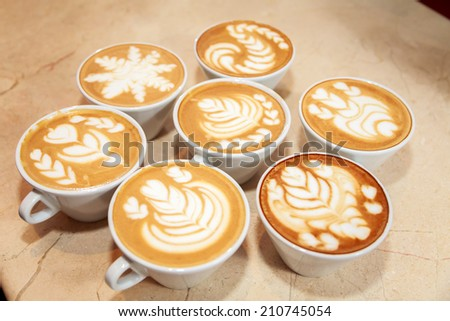 Cup of cappuccino at the table. Cappuccino with a beautiful drawings are on the table. Cup of coffee, frothy milk, spoon, cinnamon. Concept catering. Idea of the article about coffee. - stock photo