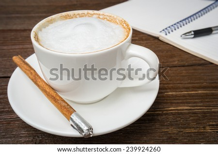 Cup of cappuccino coffee and book  - stock photo