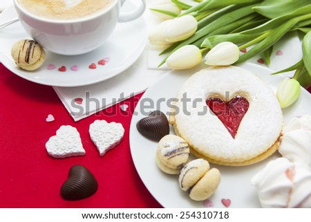 Cup of cappuccino coffee on the red napkin with heart shaped decorations, flowers and assorted sweets for Valentine's Day. Lovers breakfast. - stock photo