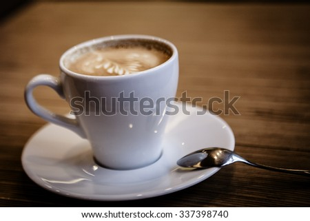 Cup of Cappuccino Coffee on wooden table - stock photo