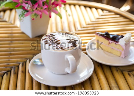 Cup of cappuccino coffee with cake