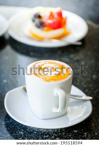 Cup of cappuccino coffee with sweet fruit tart cake on disc