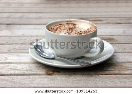Cup of Cappuccino on wooden slat table with chocolate