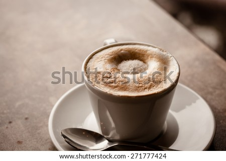 cup of cappuccino over wooden table - stock photo