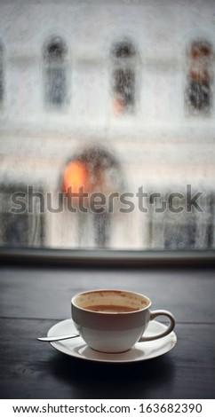 cup of cappuccino, rain fall - stock photo