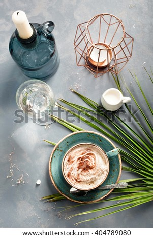 Cup of cappuccino set with modern and exotic accessories - palm leaf, candles and candle holders. Chilling out at bar by sea/ coffee consuming/holiday and travel concepts. - stock photo