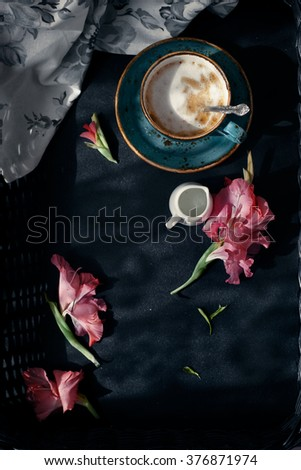 Cup of cappuccino set with pink flowers, contrast morning natural lighting, dark style photo, overview. Romantic background with retro filter effect. Toned photo. - stock photo